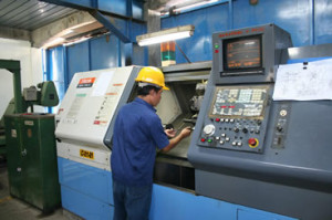 Man Working CNC Machining Lathe